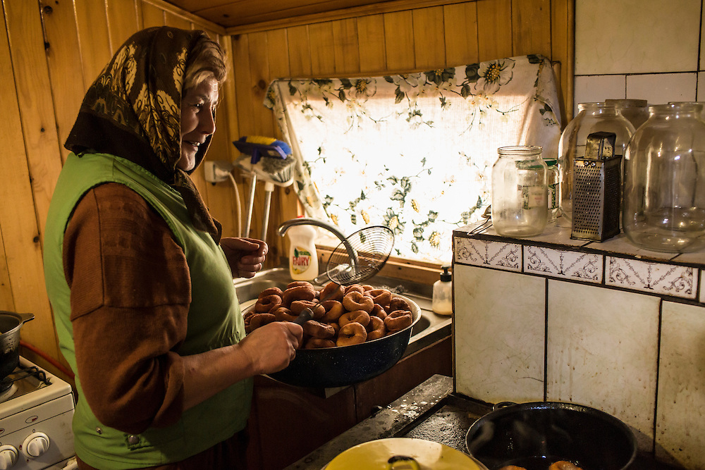 Yelizaveta Savchuk, 54, cooks ponchiki that will be consumed as a chaser for samogon, a home-made vodka, during the Malanka Festival on Wednesday, January 13, 2016 in Krasnoilsk, Ukraine. The festival begins at sundown and will last until the following evening.