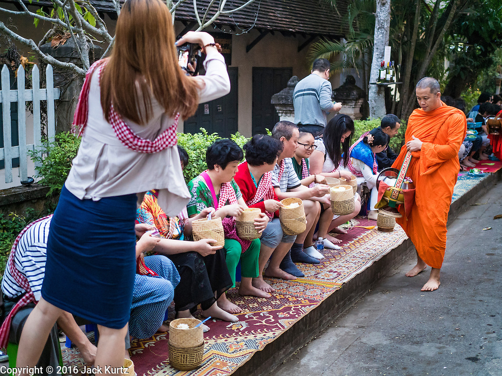 """12 MARCH 2016 - LUANG PRABANG, LAOS: Tourists give alms to and photograph Buddhist monks during the morning tak bat in Luang Prabang. Luang Prabang was named a UNESCO World Heritage Site in 1995. The move saved the city's colonial architecture but the explosion of mass tourism has taken a toll on the city's soul. According to one recent study, a small plot of land that sold for $8,000 three years ago now goes for $120,000. Many longtime residents are selling their homes and moving to small developments around the city. The old homes are then converted to guesthouses, restaurants and spas. The city is famous for the morning """"tak bat,"""" or monks' morning alms rounds. Every morning hundreds of Buddhist monks come out before dawn and walk in a silent procession through the city accepting alms from residents. Now, most of the people presenting alms to the monks are tourists, since so many Lao people have moved outside of the city center. About 50,000 people are thought to live in the Luang Prabang area, the city received more than 530,000 tourists in 2014.       PHOTO BY JACK KURTZ"""