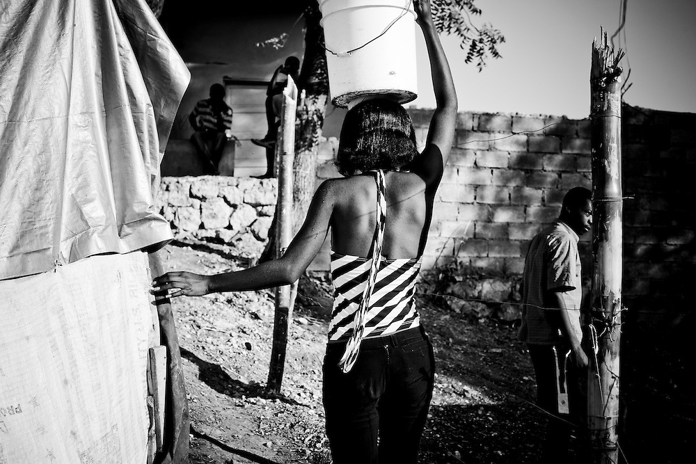 A woman carries a bucket of water on her head in a camp for those displaced by the recent earthquake in Petionville, outside Port-au-Prince, Haiti.