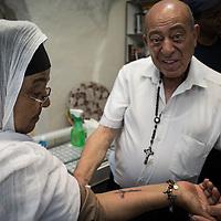 Il padre di Wassim, Antone si prende cura dei pellegrini al termine del tatuaggio