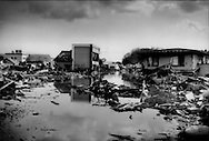 A main road flooded by the quake-triggered tsunami with buildings whose original locations were likely not where they rest now.  Kesennuma, Miyagi Prefecture, Japan.