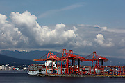 The red cranes of the Port of Vancouver, busy in action as they unload a cargo ship