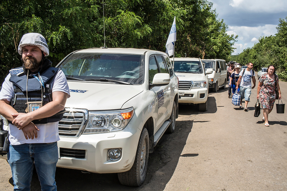 ZAITSEVE, UKRAINE - JULY 9, 2016: OSCE monitoring team patrol leader Piotr Szczepaniak from Poland, left, listens to a conversation between team members and a Ukrainian soldier at a checkpoint between Ukrainian government-controlled territory and the rebel-held Donestk People's Republic in Zaitseve, Ukraine. The mission tracks violations of the Minsk-II ceasefire agreement, among other tasks. CREDIT: Brendan Hoffman for The New York Times