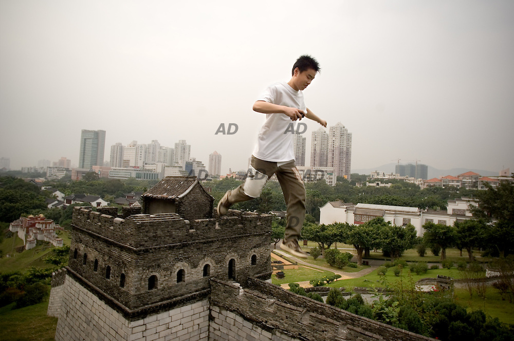 "The park ""Splendid China"" spreads almost 300,000 square meter of land. Its miniature scenic area is a replica of China, reflecting long-standing history and ancient architecture, as well as the customs and habits of 56 nationalities in China. *** Local Caption *** Boy jumps on the Great Wall in miniature. On the background the skyscrapers of Shenzhen."