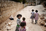 SYRIA, Idlib province: Children walk down a street in Killi, a town in Idlib province, a few days after troops of the Al Assad regime entered  the village to destroy and burn houses of allegedly pro revolution activists on April 11, 2012. ALESSIO ROMENZI