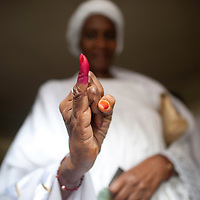 Senegalese woman pauses with her marked finger after voting in the presidential elections at a polling station in a Franco-Arab School in Point E area of Dakar..Hundreds of people, queueing for voting since the early hours, insulted and heckled the president and candidate Abdoulaye Wade during his vote casting at the poll station, accusing the head of state of disrespect for the country's constitution when running for a third term in office..Tensions between opposition supporters and security forces have been high in the capital Dakar and other cities around the country since Wade announce his candidature late July. Some violent clashes culminated with the death of 12 people and many injured in the past month alone. ©Sylvain Cherkaoui