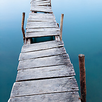 A long exposure smooths out the colorful ocean water as leading lines lead you down a dock as if it is floating in air, as if you were dreaming.