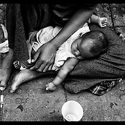 A Cambodian woman with baby begs money at a bus stop in downtown Bangkok.  Illegal immigrants from Cambodia are often part of begging gangs in the Thai capital.