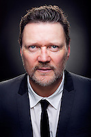 Ian Puleston-Davies Theatrical actor headshot in colour. Ian is wearing rock and roll teddy boy type suit with white shirt and thin black tie
