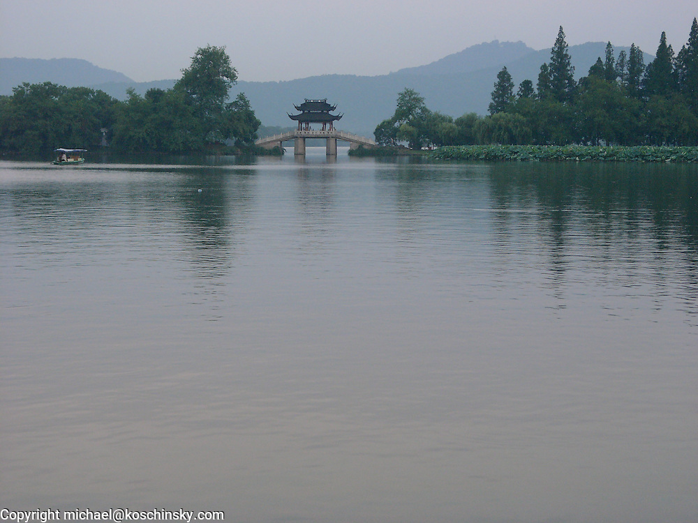 Chinese bridge over waterway embedded in parc, Hangzhou,wide angel
