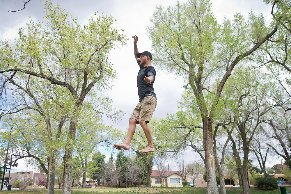 """mkb032317/metro/Marla Brose --  """"It's so much fun. It feels like you're floating,"""" said Spencer Langefeld, after walking about 150 feet on a slack line that ran from two large budding oaks in Roosevelt Park, Thursday, March 23, 2017, in Albuquerque, N.M. Langefeld was one of a number of slack liners who frequent Roosevelt Park. The slack liners agreed that spring is one of the best times for the sport, except for the wind, which they said, makes balancing more challenging. (Marla Brose/Albuquerque Journal)"""