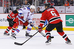 Oct 21, 2014; Newark, NJ, USA; New York Rangers defenseman Ryan McDonagh (27) skates with the puck while being defended by New Jersey Devils defenseman Andy Greene (6) during the first period at Prudential Center.