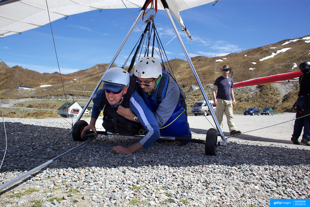 Anders Palmqvist (left) instructs tourist Raj Sharma from New York before their tandem Hang Glider flight from Coronet Peak, Queenstown, New Zealand. 7th November, 2011