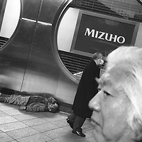 Homeless man sleeps on the pavement outside of a Mizhuo bank in Shinjuku, Tokyo, Japan. 2004