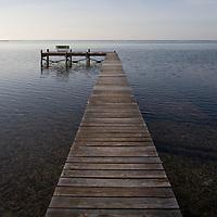 Cayman Islands, Little Cayman Island, Morning sun lights boat pier along Caribbean Sea