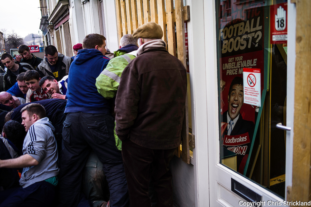 A ruck takes place outside the betting shop Ladbrokes on the high street. Prize money is up for grabs from the ba' donor for each goal scored.