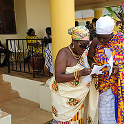 Mama Agblatsu III (left), a Queen Mother from Ho in the Volta Region of Ghana, conferring with a colleague ahead of assuming a role as Master of Ceremonies at a swearing-in ceremony for newly elected members of a council of Queen Mothers in Accra, Ghana on 23 June 2015. A queen mother is a traditional female leader, drawn from the relevant chiefly lineage, who is responsible for women's and children's issues in particular. Though often widely respected and sometimes powerful, especially in matrilineal ethnic groups, their authority is subject to a male chief. After being suppressed during the colonial era, the role of queen mother is being revived in Ghana and is seen by many as a force for development.
