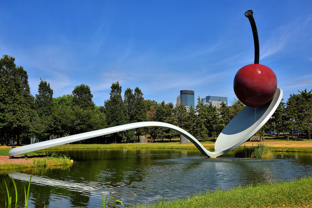 Spoonbridge and Cherry Sculpture by Claes Oldenburg in Minneapolis, Minnesota<br /> In 1988, Claes Oldenburg, along with his wife Coosje van Bruggen, created this delightful, oversized sculpture called Spoonbridge and Cherry for the Walker Art Center.  The spoon weighs 5,800 pounds and the cherry with the water streaming from it is 1,200 pounds.  It is one of 40 outdoor artworks in the Minneapolis Sculpture Garden.