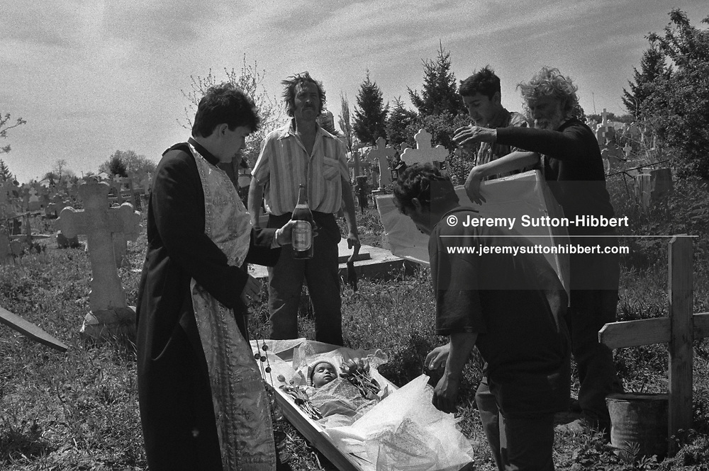 The funeral of Florin Mihai, aged 4, who died of meningitis in the Kalderash Roma camp of Sintesti, near Bucharest. HIs family were poor and could barely afford the funeral. Florin was buried wearing his favourite woollen cap, along with some flowers and a little money. The Romanaina Orthodox priest pours beer over the cofin as he says funeral rites.