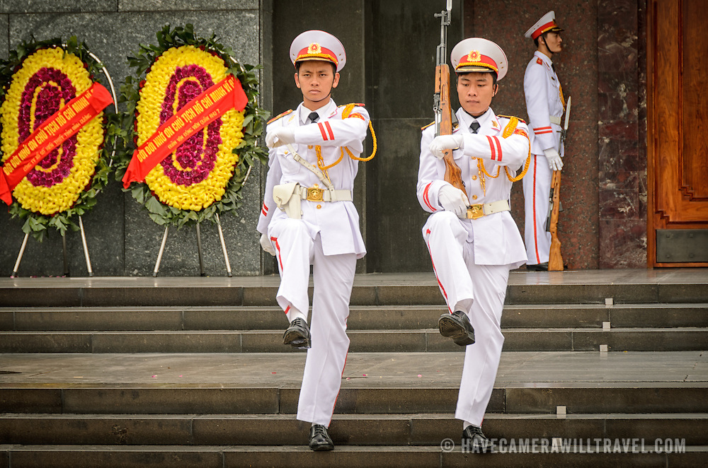 Two soldiers goose step their way from the entrance of the Ho Chi Minh Mausoleum at the end of the changing of the guard ceremony. A large memorial in downtown Hanoi surrounded by Ba Dinh Square, the Ho Chi Minh Mausoleum houses the embalmed body of former Vietnamese leader and founding president Ho Chi Minh.