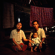 """Karen couple: Ler Lay Kler (32) with his wife Shirley (29) and their child Cherry (14 months old), inside their house at Mae La refugee camp. Ler Lay comes from Mon state in Burma and has been to the camp since 1993. Shirley has been at the camp since 2005. They met and got married in the camp. .Burmese refugee camp """"Mae La"""" is north of border-town Mae Sot and lies along the Thai-Burmese border on the side of Thailand. Approximately 50,000 people live there. 38,167 was the official number of registered people in November 2009, according to the Thailand Burma Border Consortium (TBBC), and the rest are unregistered or people who come and go."""