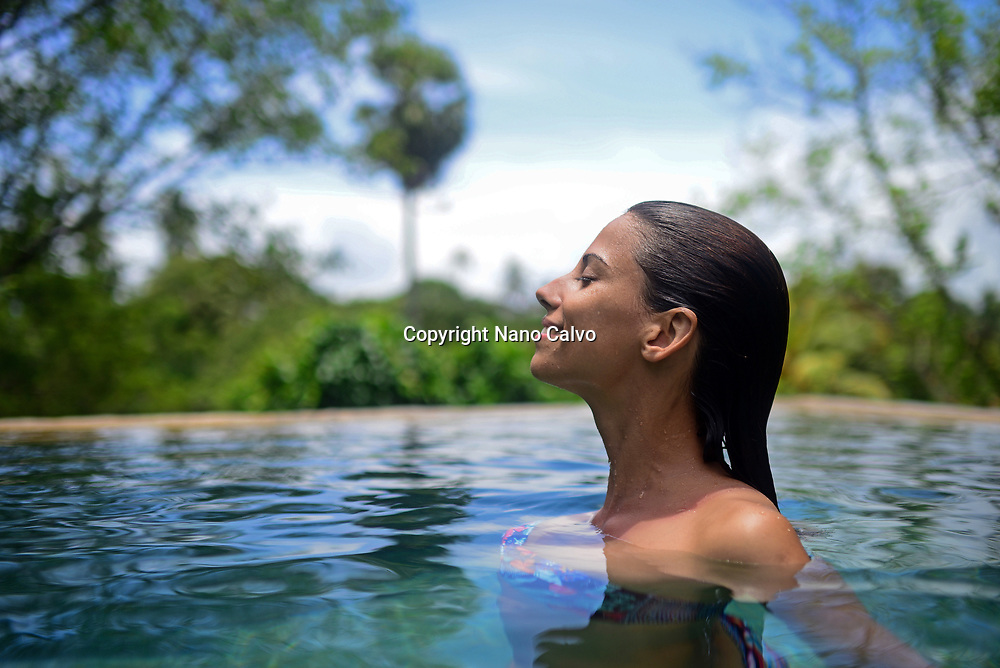 Young attractive woman enjoying a bath in the infinity edge swimming pool at The Dutch House, Galle, Sri Lanka