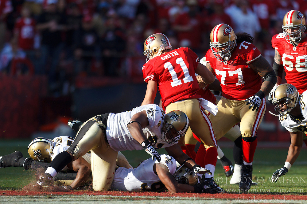 Jan 14, 2012; San Francisco, CA, USA; San Francisco 49ers quarterback Alex Smith (11) fumbles the ball against the New Orleans Saints during the second quarter of the 2011 NFC divisional playoff game at Candlestick Park. Mandatory Credit: Jason O. Watson-US PRESSWIRE