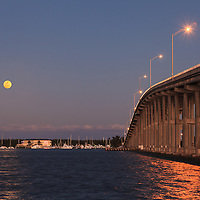 The full moon rises over Virginia Key behind the William M. Powell Bridge. The bridge connects the Florida mainland to Key Biscayne and Virginia Key as part of Miami's Rickenbacker Causeway. The bridge is also effectively the highest hill in South Florida at 80 feet in height.