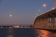 The full moon rises over Virginia Key behind the William M. Powell Bridge. The bridge connects the Florida mainland to Key Biscayne and Virginia Key as part of Miami's Rickenbacker Causeway. The bridge is also effectively the highest hill in South Florida at 80 feet in height.<br /> WATERMARKS WILL NOT APPEAR ON PRINTS OR LICENSED IMAGES.