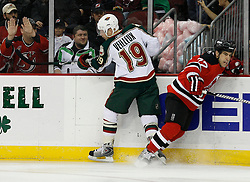 Mar 20, 2009; Newark, NJ, USA; Minnesota Wild left wing Stephane Veilleux (19) hits New Jersey Devils defenseman Mike Mottau (27) during the first period at the Prudential Center.