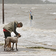 Jamie Horal pats his dog Jake as the two play on a submerged road on the edge of Cedar Key, Florida in preparation for Tropical Storm Alberto June13, 2006. Horal was vacationing in Cedar Key. REUTERS/Scott Audette