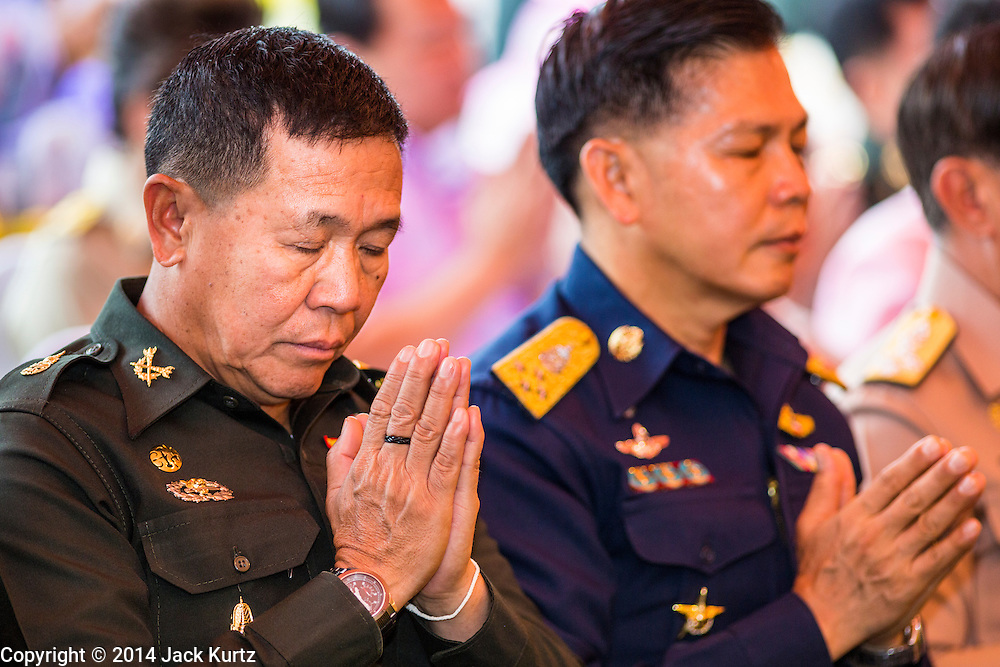 """22 JULY 2014 - BANGKOK, THAILAND: Thai Army and Air Force officers representing the ruling junta pray during a religious service at Sanam Luang. Hundreds of Thai military officers and civil servants attended a Buddhist chanting service and merit making ceremony to mark the 2nd month anniversary of the May 22 coup that deposed the elected civilian government and ended nearly six months of sometimes violent anti-government protests. The ruling junta said the ceremonies Tuesday were the kickoff to a """"Festival to Bring Back Happiness of the People of the Nation."""" There will be free concerts, historical pageants and movies at Sanam Luang, a large parade ground near the Ministry of Defense in Bangkok.    PHOTO BY JACK KURTZ"""