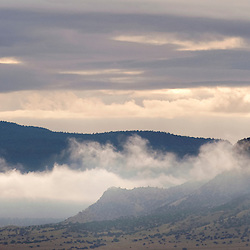 The fog begins to lift at the base of Mount Taylor on a cool fall morning.