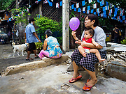 16 MAY 2017 - BANGKOK, THAILAND: A woman and her grandson sit in what used to be a home and is now an empty lot in Pom Mahakan. The city evicted the family living in the home and tore it down. The final evictions of the remaining families in Pom Mahakan, a slum community in a 19th century fort in Bangkok, have started. City officials are moving the residents out of the fort. NGOs and historic preservation organizations protested the city's action but city officials did not relent and started evicting the remaining families in early March.           PHOTO BY JACK KURTZ