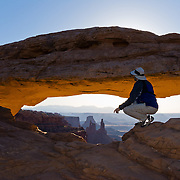 Mesa Arch frames buttes back lit by sunrise at Canyonlands National Park, Utah, USA.