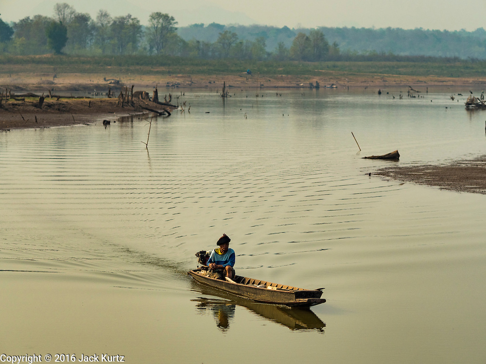 31 MARCH 2016 - NA SAK, LAMPANG, THAILAND: A fisherman guides his canoe up a stream in the bottom of the Mae Chang Reservoir. This part of the reservoir is normally completely full of water. The Mae Chang Reservoir in Lampang province was created more than 30 years ago when the Chang River was dammed. Five villages along the river were relocated to hillsides above the river. For the first time since it was flooded, the reservoir is nearly empty and the ruins of the old villages are visible. Many people who remember the old villages are coming down to the ruins to visit them. This part of Thailand hasn't received significant rain in months and many irrigation canals and streams are running dry.    PHOTO BY JACK KURTZ