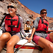 Rafters Kate Harvey and Laura Lingeman enjoy the boat handling of guide Kelly Wagner during a river trip down the Colorado River in Westwater Canyon Utah.