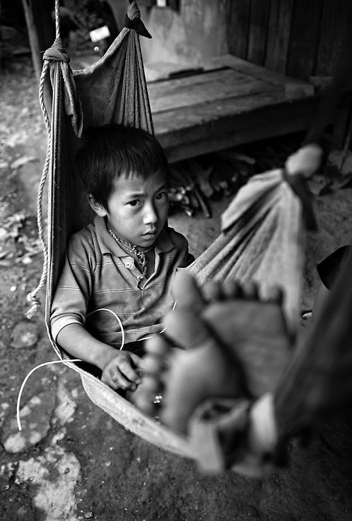A Hmong boy relaxes at home in the mountains near Luang Prabang, Laos.