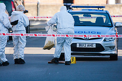 Queens Park, London,October 8th 2015. Police have cordoned off several roads as scene of crime detectives carry out their forensic investigation, following the shooting of a man allegedly armed with a knife, by officers after attempts to taser him failed. The shot man was taken to hospital. PICTURED: Forensic detectives collect evidence on Fifth Avenue at the scene of the shooting.  Contact: paul@pauldaveycreative.co.uk Mobile 07966 016 296