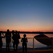 Tourists watching the sunset over the river with a crescent moon above from the rail of the ferry. Jamestown-Scotland Ferry on the James River at Dusk. Crossing from Surry County to James City County.