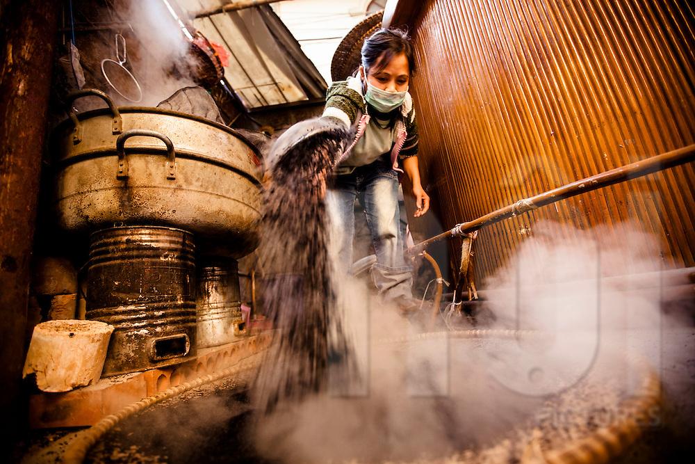 A vietnamese woman steams black sesame seeds, Vietnam, Southeast Asia