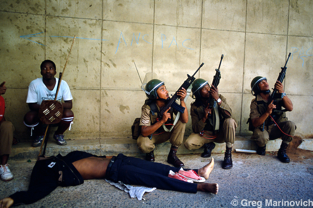 Johannesburg, South Africa, 1994.Soldiers and IFP warriors look for the hidden gunmen after  Inkatha Freedom Party marchers were killed in Library Gardens, Johannesburg 1994. Many IFP supporters killed and wounded. Others were shot from the rooftops by persons unknown at the nearby Library Gardens. Johannesburg, South Africa