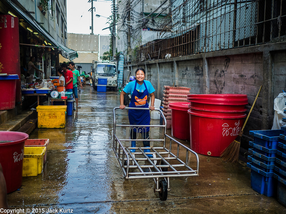 14 AUGUST 2015 - BANGKOK, THAILAND: A woman pushes a hand cart through an alley in Saphan Pla fish market in Bangkok. Saphan Pla fish market is the wholesale fish market that serves Bangkok. Most of the fish sold in Saphan Pla is farmed raised fresh water fish. The market is open 24 hours but it's busiest in the middle of the night and then again from about 7.30 until 11 in the morning.       PHOTO BY JACK KURTZ