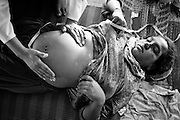 A midwife checks the growth and position of Hamida's 4th baby in a tent in a refugee camp for flood victims. <br /> The Pakistani Medical Association (PMA) provided free care for a number of camps and treats the displaced communities in the camps. For the majority of pregnant women in the camp, coming from rural villages of the interior or North of Pakistan, this is the first time they receive prenatal care and regular checkups during their pregnancy. Karachi, Pakistan, 2010