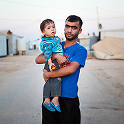 2015 July &mdash; Jordan. Zaatari Camp for Syrian Refugees. Showkat, 20, arrived three years ago from Daraa. He is pictured with his son Omer, 1 &frac12;. <br /> <br /> Life in summer: &ldquo;In the summer there&rsquo;s heat, dust, and no electricity&ndash;it makes you feel desperate. The lack of water, the dust, the heat&ndash;it makes us more tough, we become angry and behave badly in the community; we have this internal psychological pressure.&rdquo;