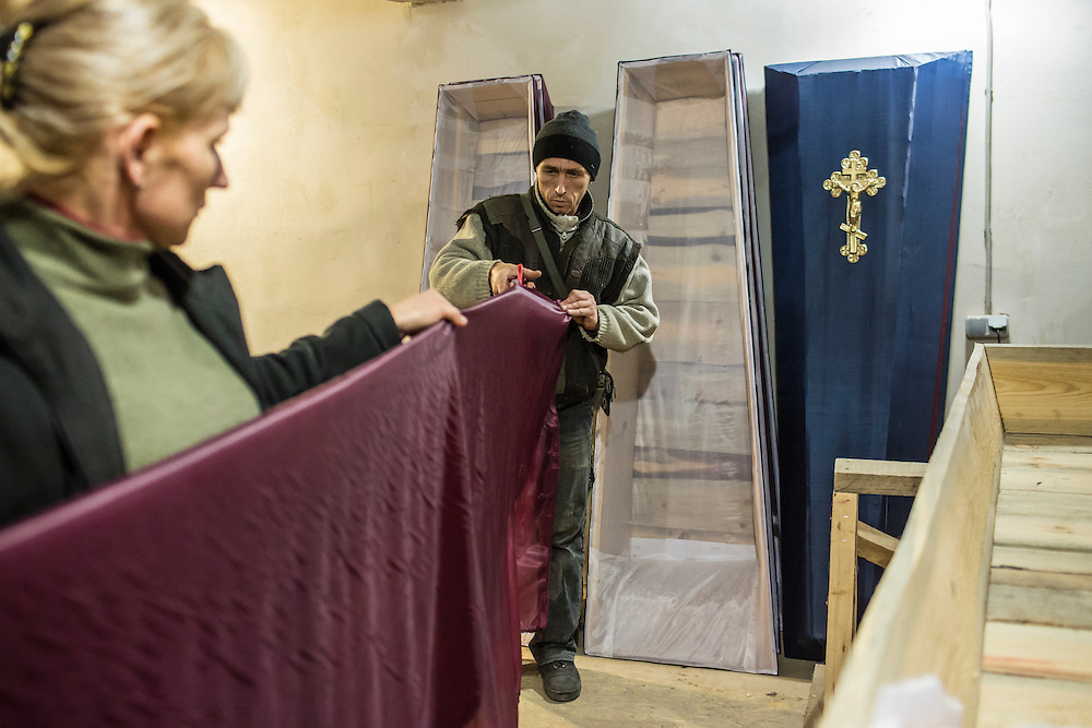 DONETSK, UKRAINE - FEBRUARY 3, 2015: Lyudmila Levochko, left, and Sergei Levohko build caskets in Donetsk, Ukraine. The city government provides basic but free or low-cost caskets for victims of shelling or others who are no longer able to afford funeral expenses, the demand for which has increased significantly in past weeks as violence has flared once again. CREDIT: Brendan Hoffman for The New York Times