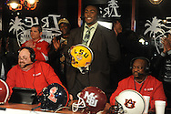"Lafayette High quarterback Jeremy Liggins (center), with hosts Ronnie Williams (left) and Fred Johnson, says ""Go Tigers, baby"" as he announces he will attend LSU during the Collier Dental Sports Roundup at the Irie in Oxford, Miss. on Monday, January 30, 2012."
