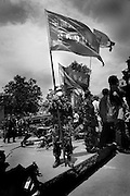 Military workers carry their regimental flags adorned withte regiment number on a background of traditional communist red.