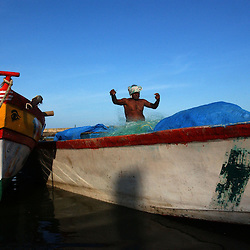 A fisherman repairs his net on one of the fibre glass boats donated to the community on Akkrapattai beach in Nagapattinum district in Tamil Nadu, India August  28,2005. The recovery process is slow and the situation still grim for many of the worlds poorest who were most affected by the deadly wave.  (Ami Vitale)