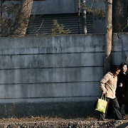 Two North Korean women walk along the the bank of the Yalu river in a in Sinuiju, North Korea on Wedenesday, Feb. 07, 2007. As The Six Party talks will resume on the 8th of February and the US hope to terminate North Korean nuclear program